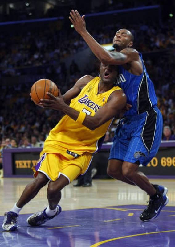El jugador de los Ángeles Lakers, Odom, trata de llegar al aro defendido por Lewis, de los Orlando Magic durante el primer partido de la final de la NBA.