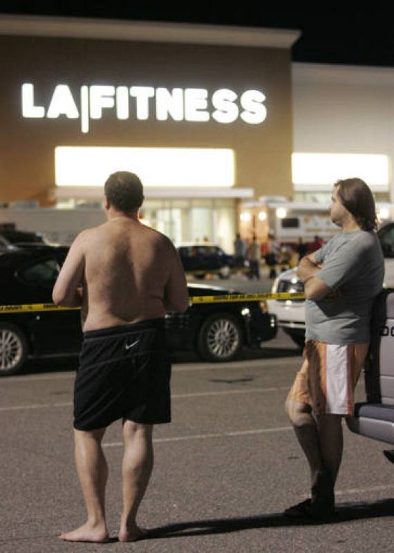 Men wait behind police lines outside the LA Fitness gym in Bridgeville
