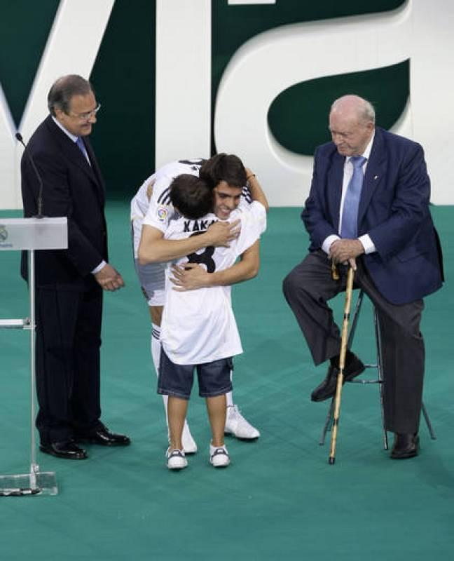 Kaká junto a Di Estéfano y Florentino durante su presentación en el Bernabéu abrazando a un niño.