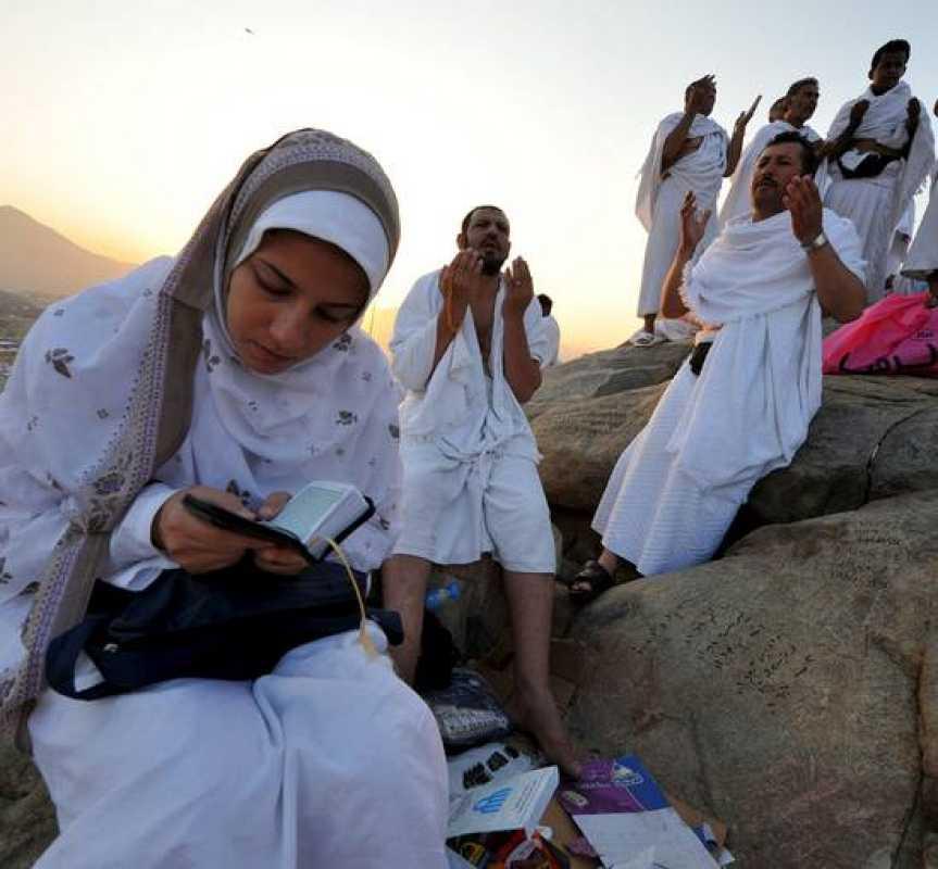 Una mujer lee el Corán mientras otros peregrinos musulmanes realizan el rezo de alba