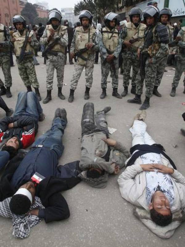 Opposition demonstrators lay in front of soldiers near Tahrir Square in Cairo