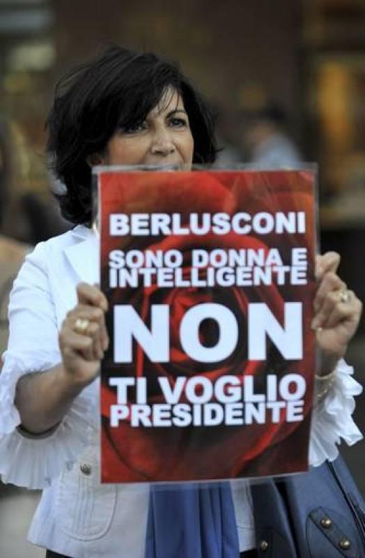 """Una mujer muestra un letrero en el que se puede leer """"Berlusconi. Soy una mujer e inteligente, no te quiero como presidente"""" durante una marcha protagonizada por la comunidad italiana en contra del primer ministro italiano, Silvio Berlusconi"""