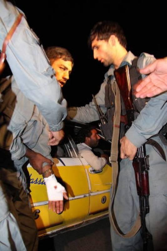 Policías afganos ayudan a un hombre herido en el atentado talibán en el Hotel Intercontinental