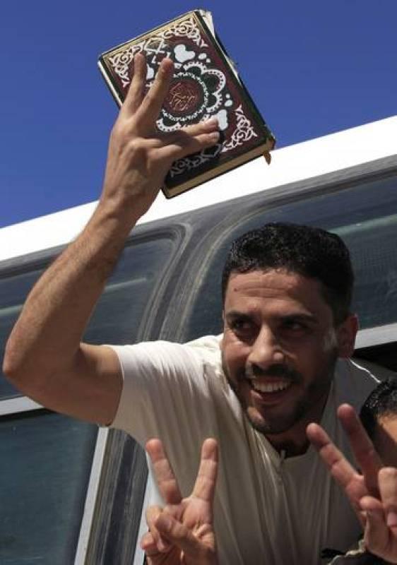 Un preso palestino excarcelado por Israel sostiene un Corán en el autobús que cruza la frontera entre Gaza y Egipto