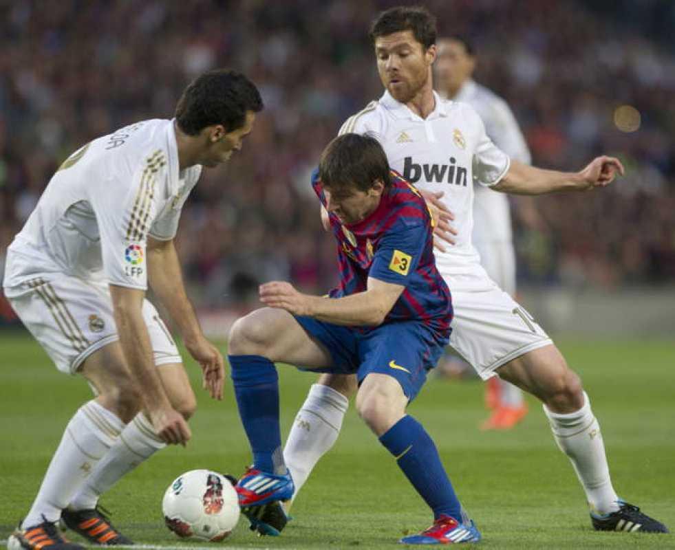 El delantero argentino del FC Barcelona Lionel Messi (c), pelea un balón con el centrocampista Xabi Alonso (detrás) y el defensa alvaro Arbeloa
