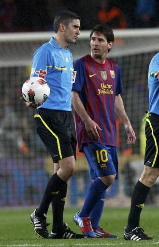 Leo Messi camina junto al colegiado Alberto Undiano Mallenco en el descanso