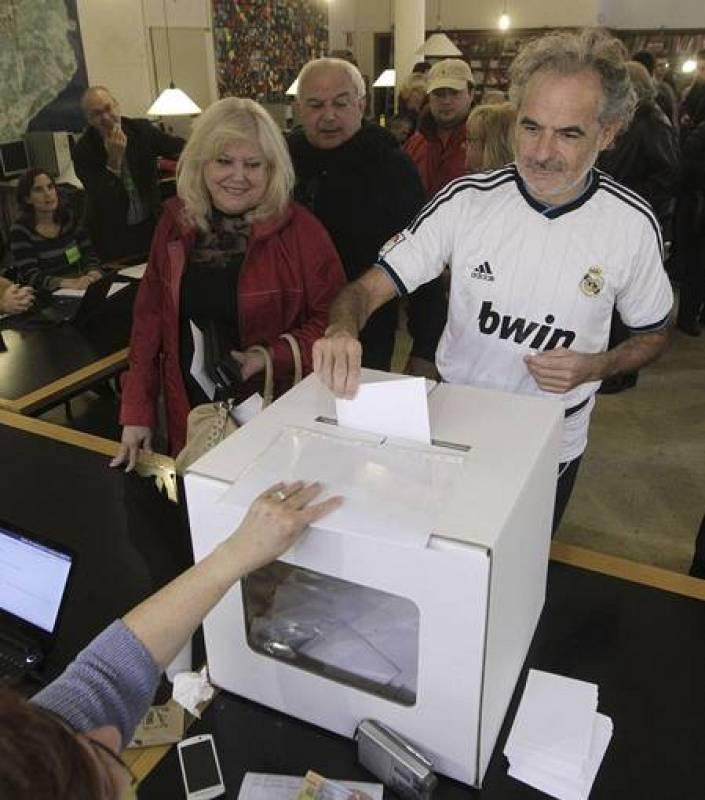 Un ciudadano, vestido con la camiseta del Real Madrid, deposita su papeleta en el Institut Montserrat de Barcelona.