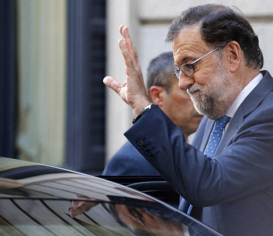 El presidente del Gobierno en funciones, Mariano Rajoy, saluda a la salida del Congreso