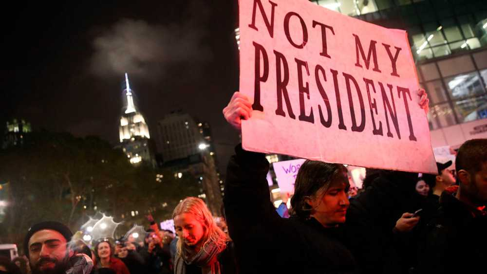 """Uno de los asistentes a la manifestación anti-Trump en Nueva York sostiene una pancarta en la que se puede leer: """"No es mi presidente""""."""