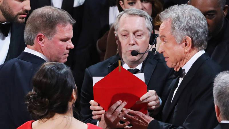 File Photo: Brian Cullinan (L) and Martha Ruiz of PriceWaterHouseCoopers (PWC) confer with presenter Warren Beatty during presentation for Best Picture