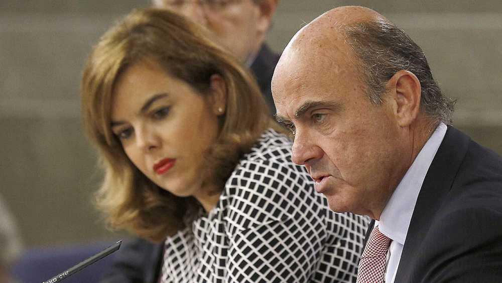 Soraya Sáenz de Santamaría junto a los ministros Rafael Catalá, (iz),y Economía, Luis de Guindos, durante la rueda de prensa posterior a la reunión del Consejo de Ministros