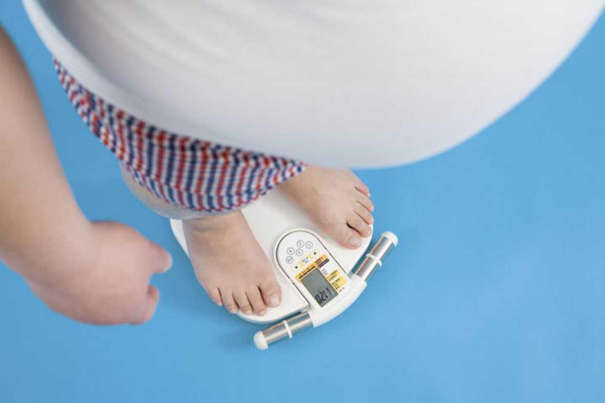 Hombre obeso pesándose en una báscula.