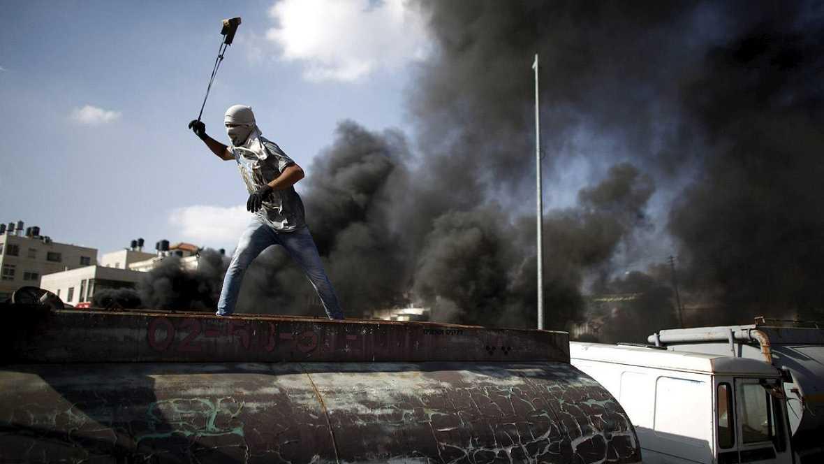 Un palestino usa una honda para lanzar piedras a los soldados israelíes en Beit El, cerca de Ramala, en Cisjordania