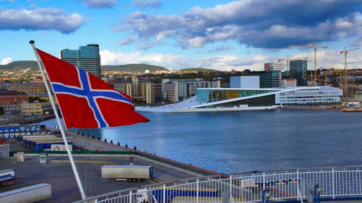 Una panorámica de Oslo con la bandera de Noruega en primer plano