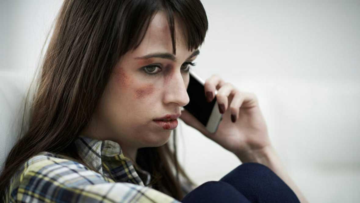 Mujer víctima de violencia de género llamando por teléfono