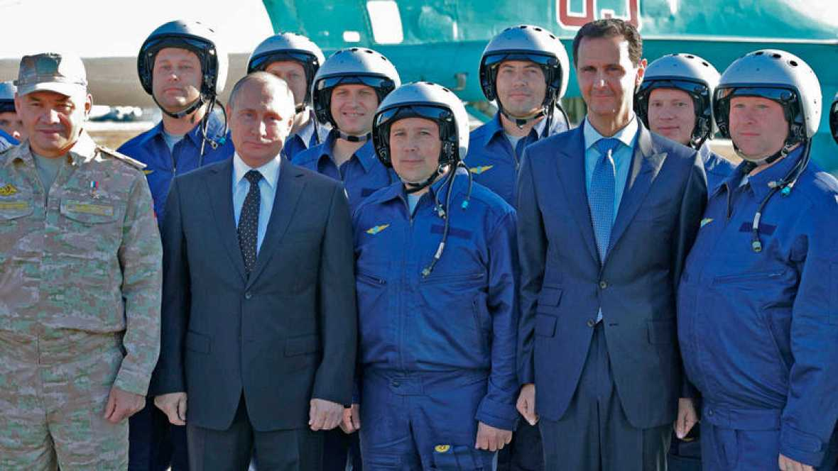 El presidente ruso, Vladímir Putin, y su homólogo sirio, Bachar al Asad, posan junto a varios soldados rusos en la base aérea rusa de Hmeimim