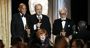 Singer and social activist Belafonte, holding the Jean Hersholt Humanitarian Award, screenwriter Carriere, actress O'Hara and Japanese film director and animator Miyazaki pose onstage at the Academy of Mot
