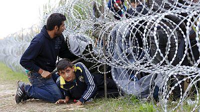 Refugiados sirios cruzan hacia Hungría bajo la alambrada metálica desplegada en la frontera con Serbia.