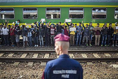 Un policía vigila mientras refugiados piden poder continuar su viaje rumbo a Europa Occidental en la estación ferroviaria de Bicske (Hungría) el pasado 4 de septiembre.