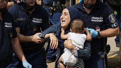 La policía desaloja a una refugiada y a su hijo de la estación de Keleti, en Budapest, a principios de septiembre.