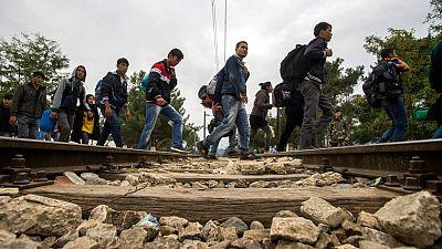 Refugiados caminan cerca de la frontera griega en Gevgelija, Macedonia