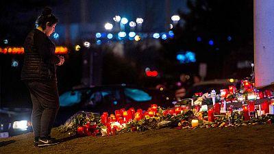 Una mujer reza en Bruselas delante de una ofrenda floral a las víctimas