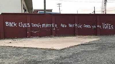 """Un grafiti que reza """"Las vidas negras no importan ni tampoco vuestros votos"""" en una calle de Durham, Carolina del Norte."""