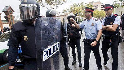 Agentes antidisturbios de la Policía Nacional y de los Mossos d' Esquadra discuten frente al Instituto Can Vilumara de L'Hospitalet de Llobregat