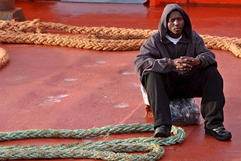 Uno de los 121 inmigrantes que viajaban en dos los dos cayucos interceptados por Salvamento Marítimo descansa a su llegada a Tenerife, tras arribar al muelle de Los Cristianos.