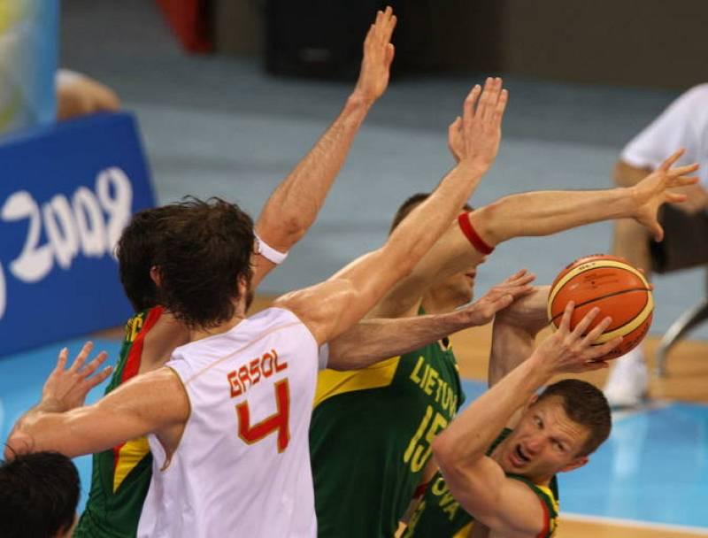 El lituano Mindaugas Lukauskis controla el balón ante el bloqueo del español Pau Gasol.