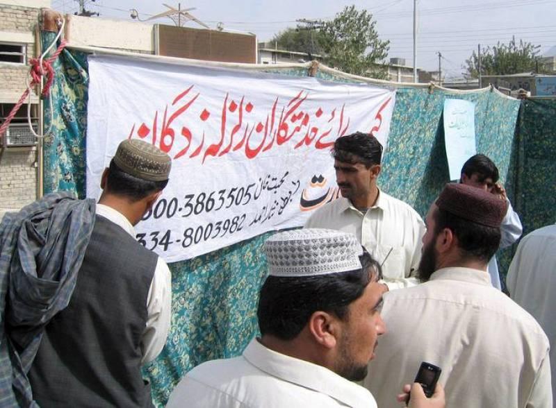 """Varias personas reunidas junto a un cartel en el que se puede leer """"Campo de ayuda para víctimas del terremoto"""" en Quetta, capital de la provincia de Balochistan (Pakistán)."""