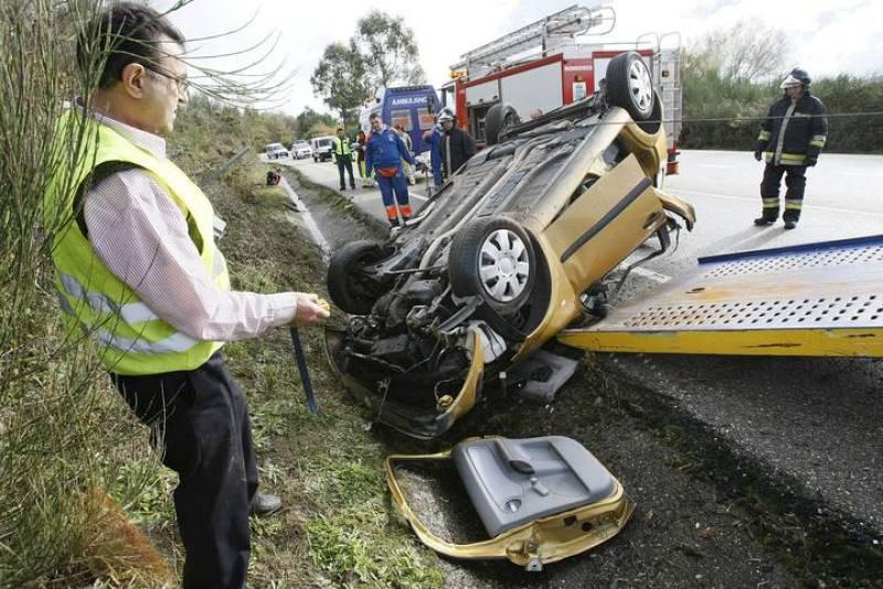 Bomberos y Guardia Civil asisten a la retirada de la carretera de Covelo del vehículo que conducía P.G.V. cuando sufrió el accidente que le costó la vida.