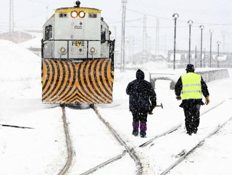 Dos operarios se acercan a una locomotora en las vias cubiertas por la nieve de la estación de Mataporquera, debido a las intensas nevadas que están cayendo en las zonas interiores de la cornisa cantábrica.