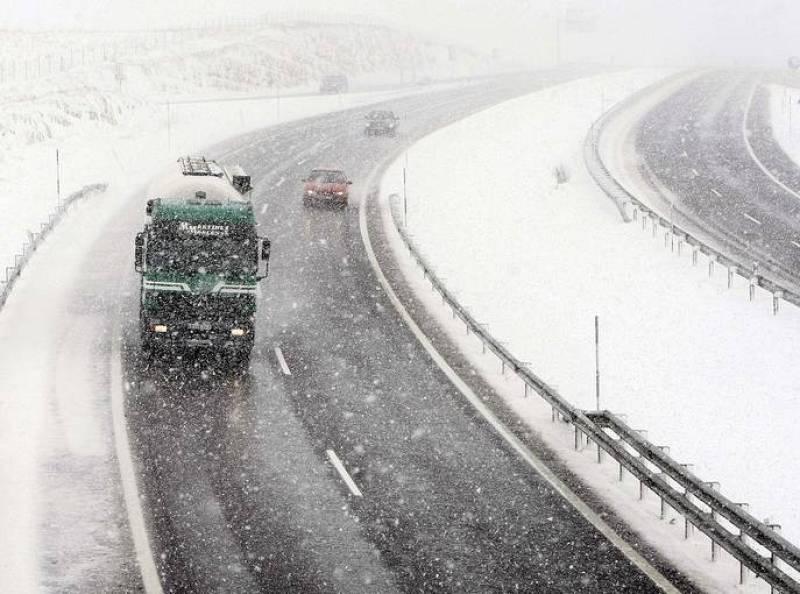 Varios vehiculos circulan por la autovía A-67 a la altura del puerto de El Pozazal en medio de una de las intensas nevadas que están cayendo en las zonas interiores de la cornisa cantábrica.