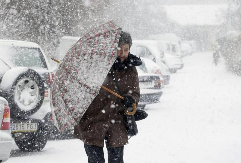 Un vecino de Soria se cobija bajo su paraguas de las intensas nevadas caídas en Castilla León