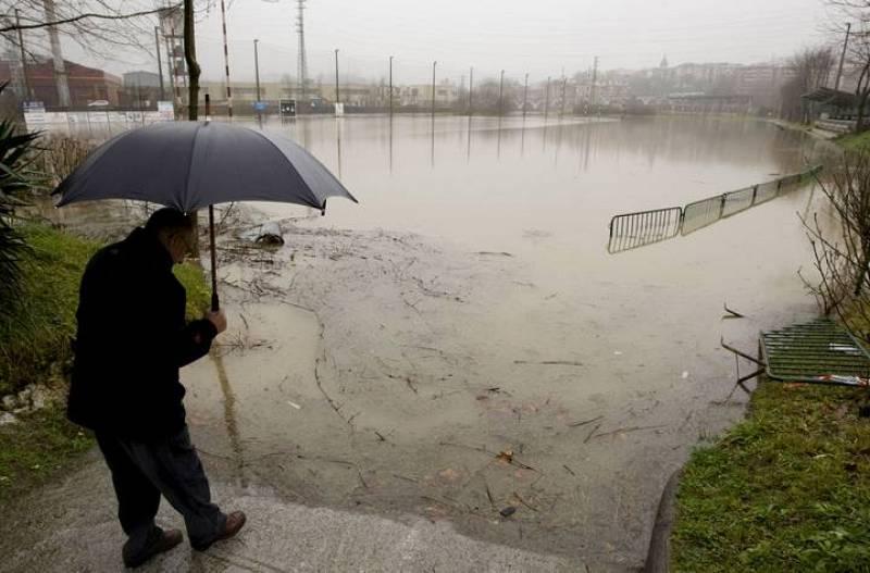 Un hombre observa un campo de rugby totalmente anegado por el agua en Hernani.