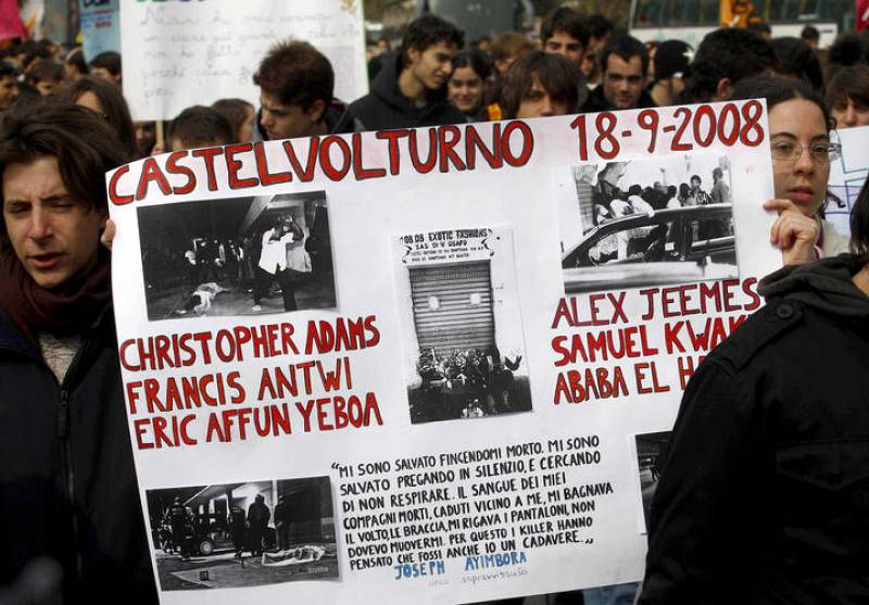Demonstrators hold a banner remembering the massacre of Castelvolturno as they march in the southern city of Naples
