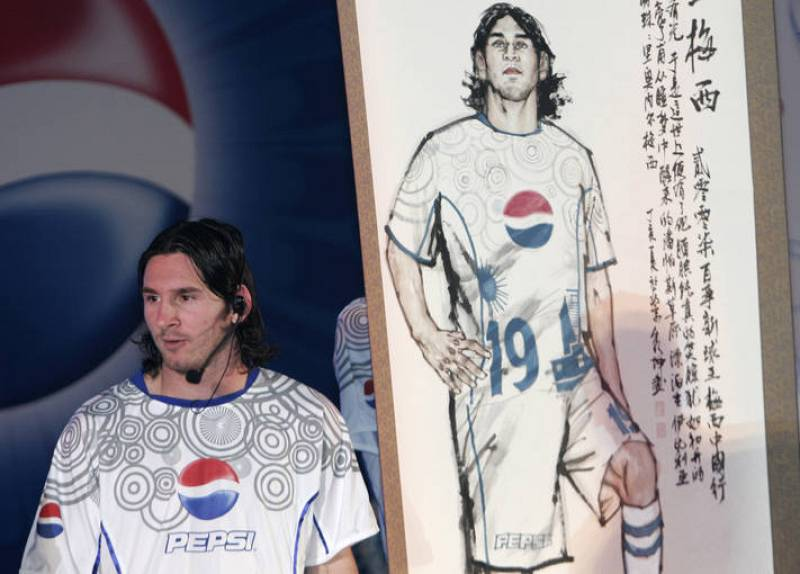 Argentina's soccer player Lionel Messi stands next to a Chinese traditional painting of himself during a promotion event in Beijing