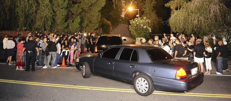 Una comitiva de coches pasa entre los fans congregados a las puertas de la residencia de la familia Jackson.