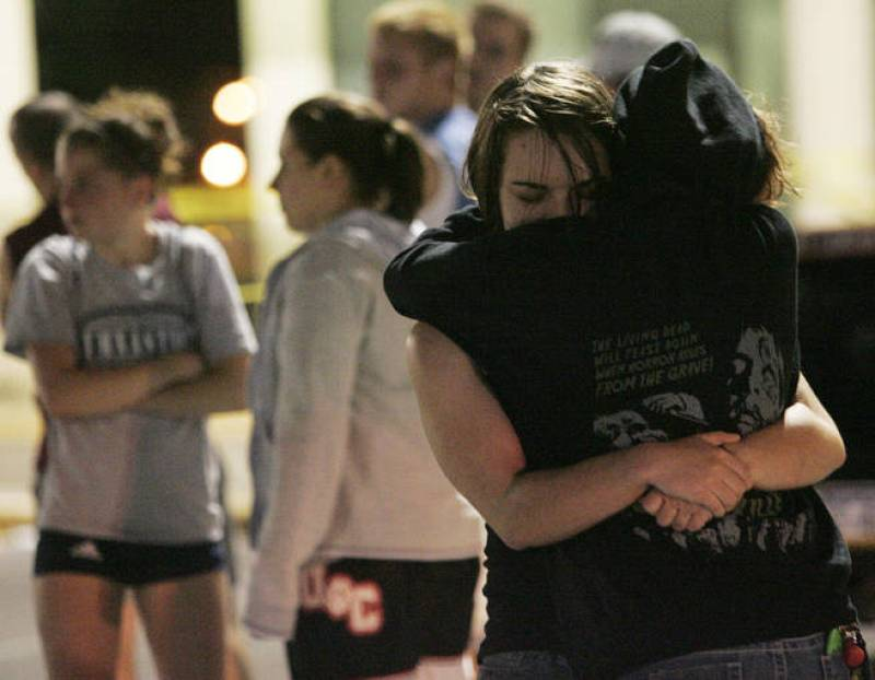 Two women hug in the parking lot outside the LA Fitness gym in Bridgeville after a shooting