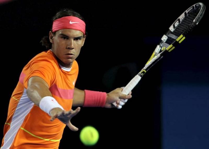 El tenista español Rafael Nadal devuelve la bola al australiano Peter Luczak durante el partido de primera ronda del Abierto de Australia de tenis.