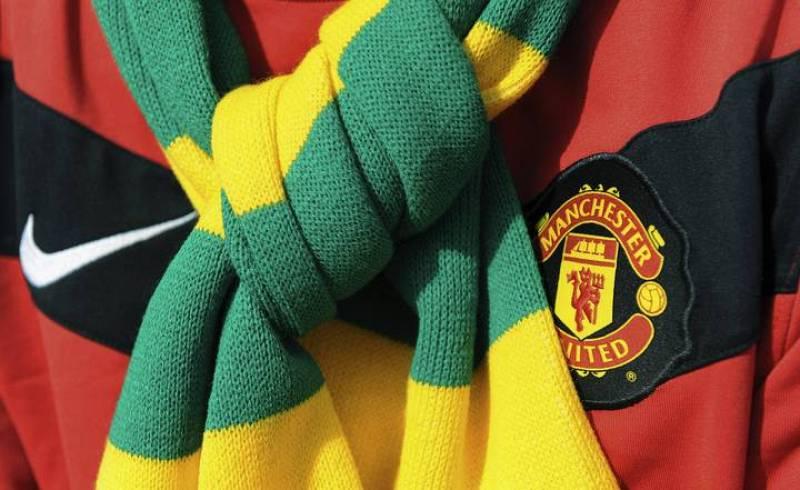 Un aficionado del United lleva una bufanda verde y dorada, los colores originarios del Manchester, en señal de protesta contra los propietarios, los hermanos Glazer.
