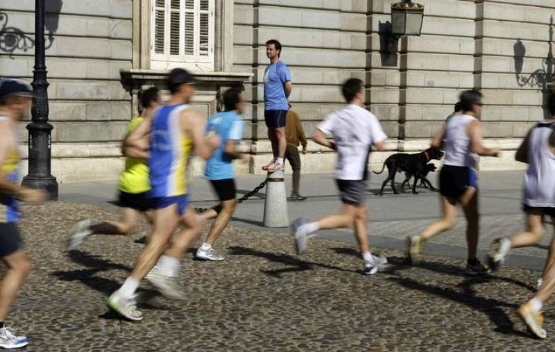 Participants run past Madrid's Royal Palace during the XXXIII Madrid marathon