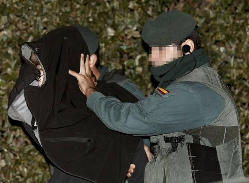 Dos guardias civiles se llevan detenida a una persona en Ansoaín