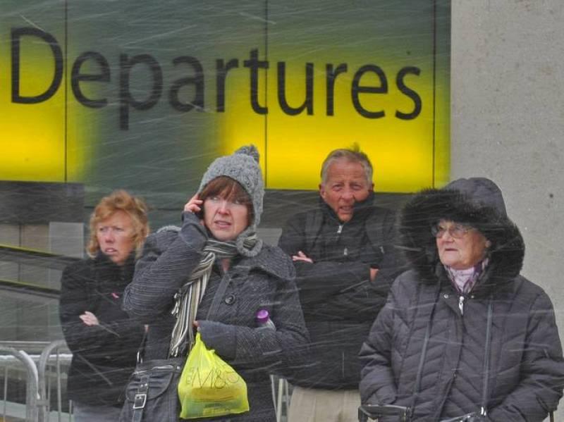 Varios pasajeros esperan en el exterior del aeropuerto de Gatwick