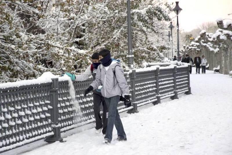 Estudiantes de instituto camino de clase por la orilla del rio Carrion, esta mañana, tras la intensa nevada de la noche que ha cubierto la ciudad de Palencia.