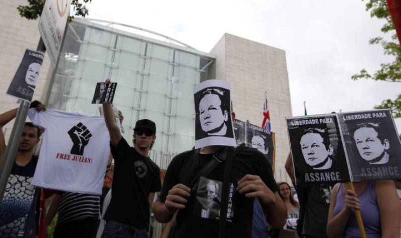 Protester holds pictures in support of WikiLeaks founder Julian Assange during a demonstration in front of the British Consulate in Sao Paulo
