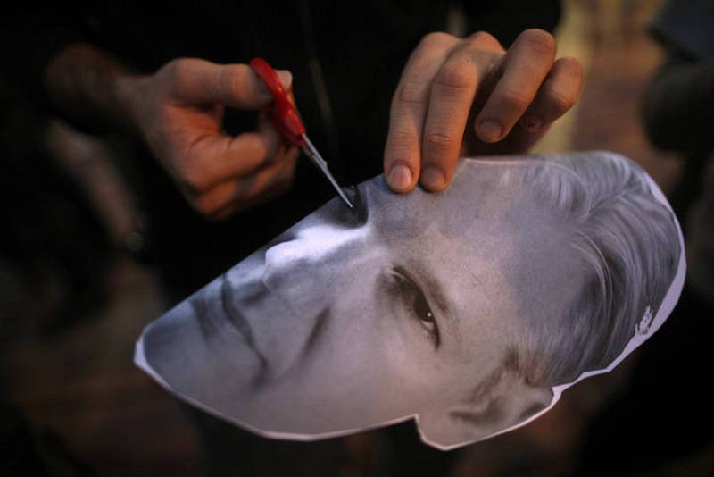 A protester cuts holes into the eyes of a mask of WikiLeaks founder Julian Assange as he takes part in a demonstration to call for the release of Assange, in Malaga