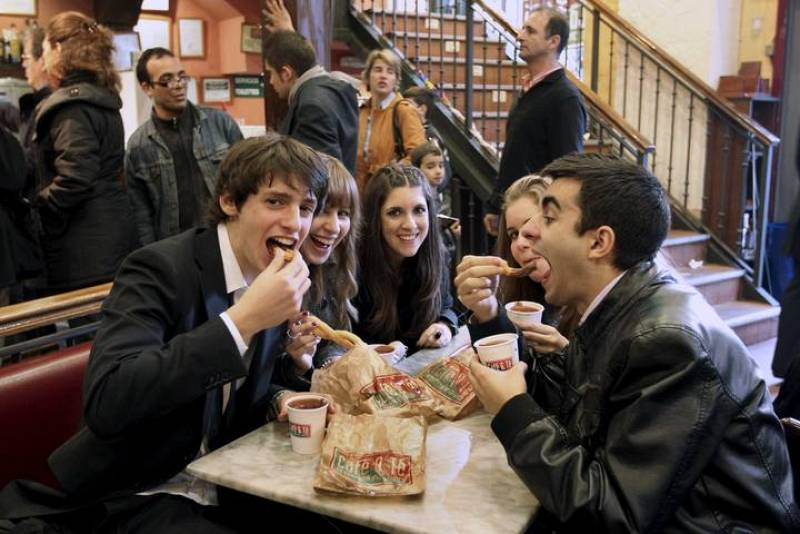 Un grupo de jóvenes toman el tradicional chocolate con churros a primeras horas de la mañana en un local madrileño, tras la celebración de la Nochevieja y el Año Nuevo la pasada madrugada
