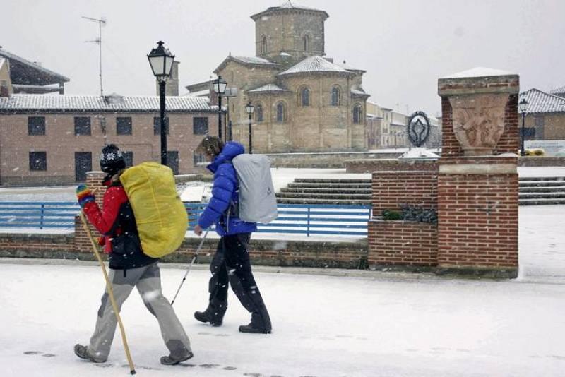 Dos peregrinos pasan por delante de San Martín en Frómista (Palencia), localidad cubierta por la nieve